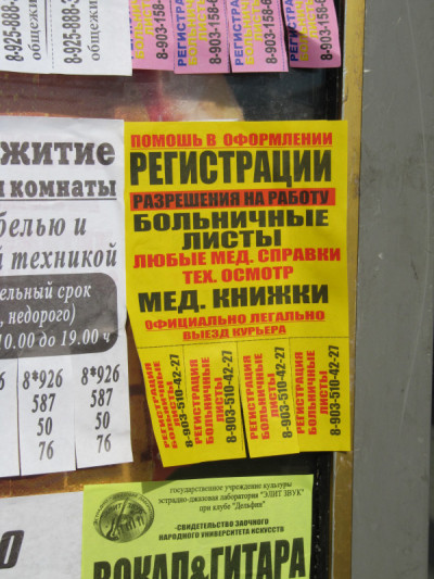 Posters advertising helping in locating the registrations, work permits, medical certificates and other documents needed by migrants to work legally in Russia. Moscow, July 2010